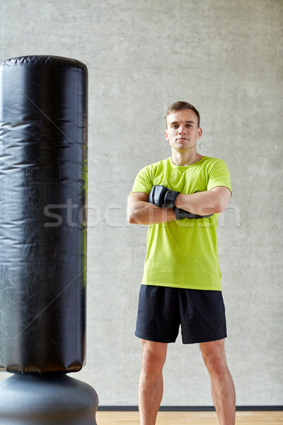 man with boxing gloves and punching bag in gym Stock photo © dolgachov