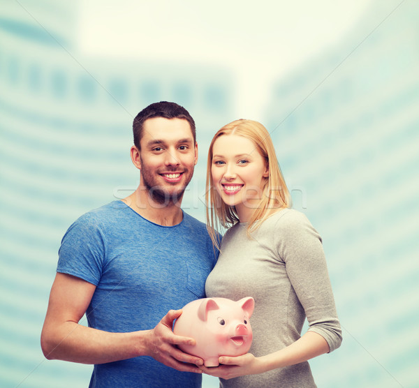 smiling couple holding big piggy bank Stock photo © dolgachov