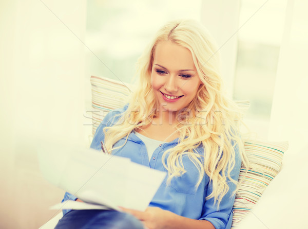 smiling young woman with papers at home Stock photo © dolgachov