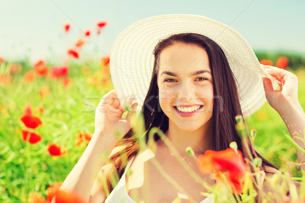 smiling young woman in straw hat on poppy field Stock photo © dolgachov