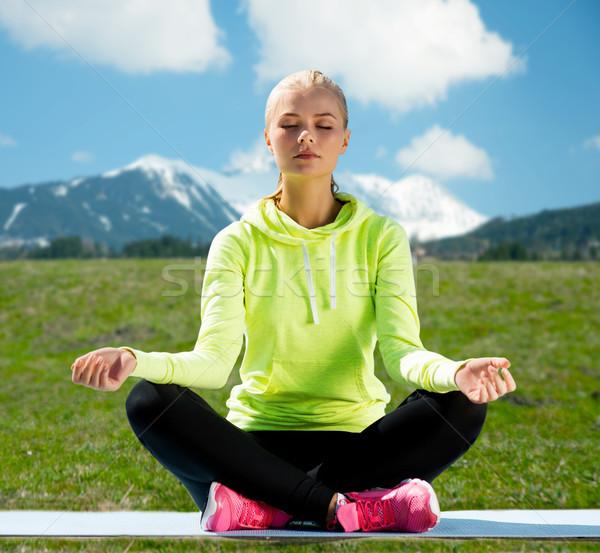 woman sitting in lotus pose doing yoga outdoors Stock photo © dolgachov