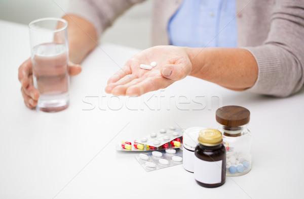 Senior donna pillole acqua età Foto d'archivio © dolgachov