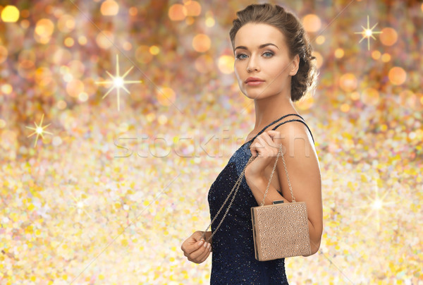 woman in evening dress with bag over golden lights Stock photo © dolgachov