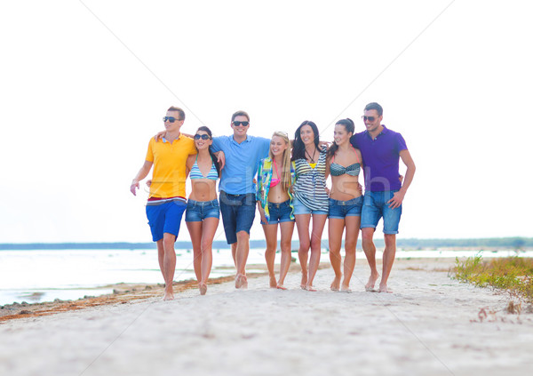 group of happy friends walking along beach Stock photo © dolgachov