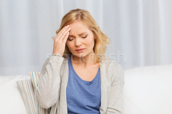unhappy woman suffering from headache at home Stock photo © dolgachov