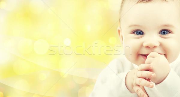 close up of happy baby over yellow background Stock photo © dolgachov