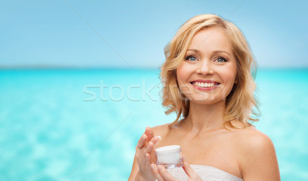 happy middle aged woman with cream jar over sea Stock photo © dolgachov