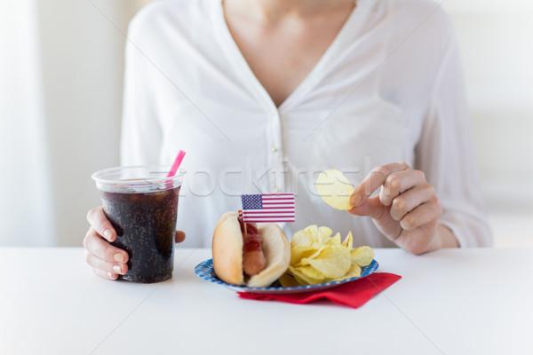 Közelkép nő eszik sültkrumpli hot dog kóla Stock fotó © dolgachov