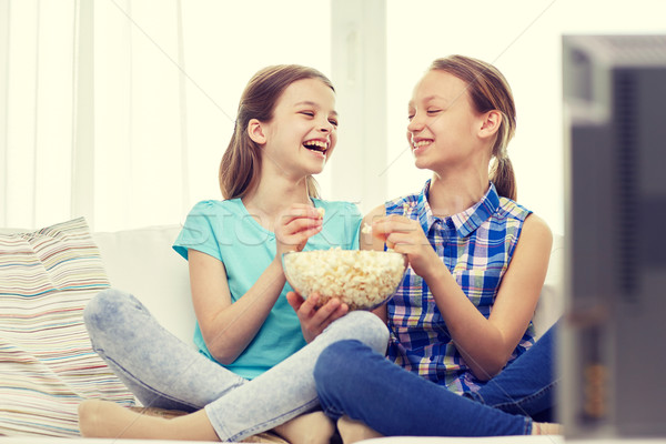 happy girls with popcorn watching tv at home Stock photo © dolgachov