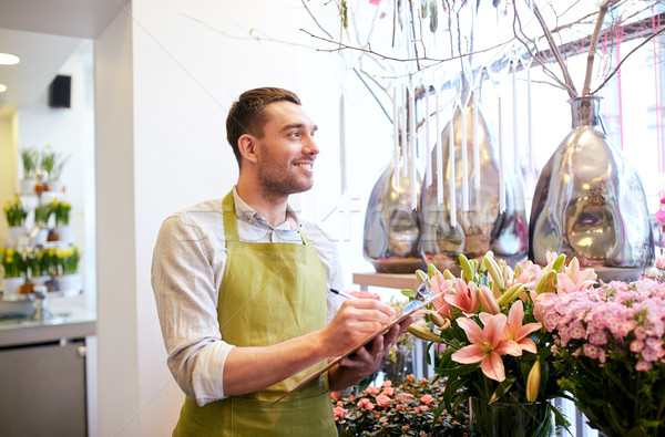 florist man with clipboard at flower shop Stock photo © dolgachov
