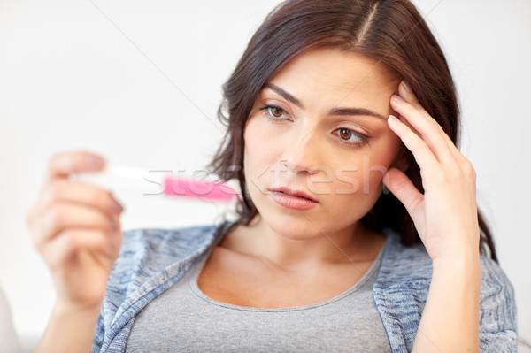 sad woman looking at home pregnancy test Stock photo © dolgachov