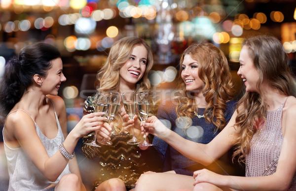 happy women with champagne glasses at night club Stock photo © dolgachov