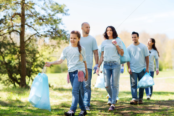 Stock photo: group of volunteers with garbage bags in park