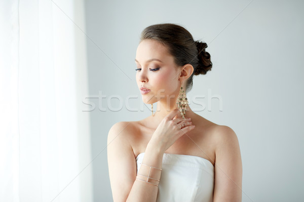 Belle asian femme boucles d'oreilles bracelet beauté Photo stock © dolgachov