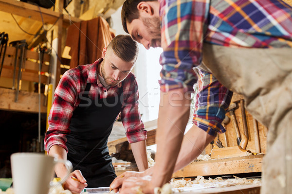 Stock photo: carpenters with ruler and blueprint at workshop