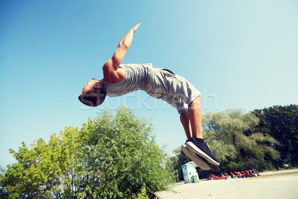 sporty young man jumping in summer park Stock photo © dolgachov