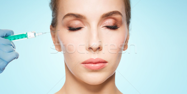 woman face and hand with syringe making injection Stock photo © dolgachov