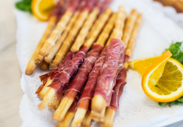 close up of grissini bread sticks with prosciutto Stock photo © dolgachov