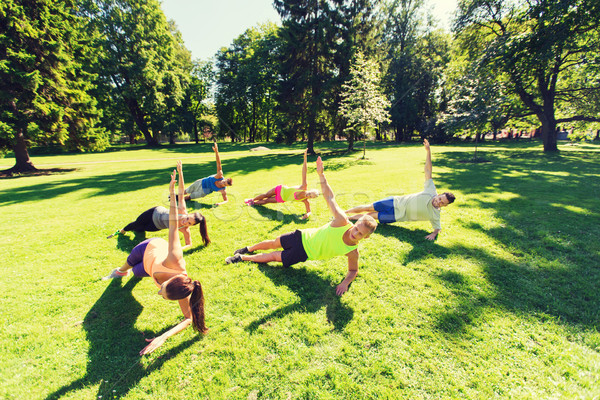 group of happy friends exercising outdoors Stock photo © dolgachov