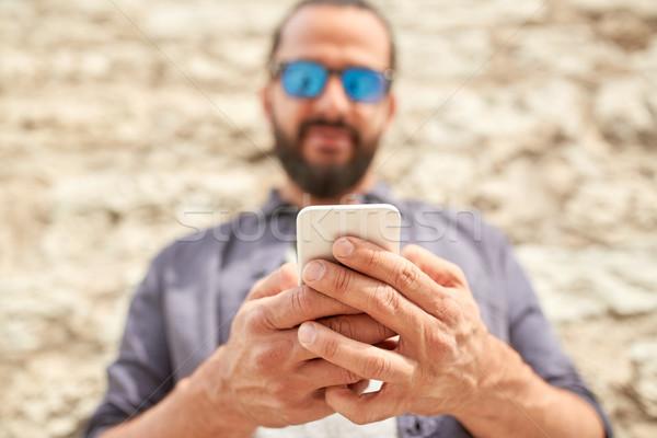Uomo smartphone muro di pietra tempo libero tecnologia Foto d'archivio © dolgachov