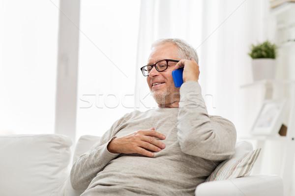 happy senior man calling on smartphone at home Stock photo © dolgachov