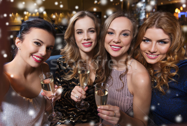 smiling women with champagne taking selfie at club Stock photo © dolgachov