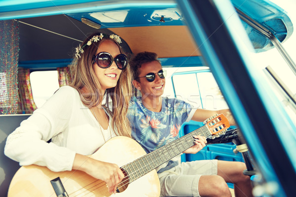 smiling hippie couple with guitar in minivan car Stock photo © dolgachov