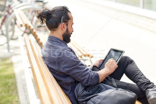man with tablet pc sitting on city street bench Stock photo © dolgachov