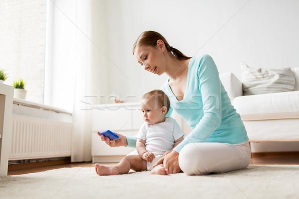 Boldog anya mutat okostelefon baba otthon Stock fotó © dolgachov