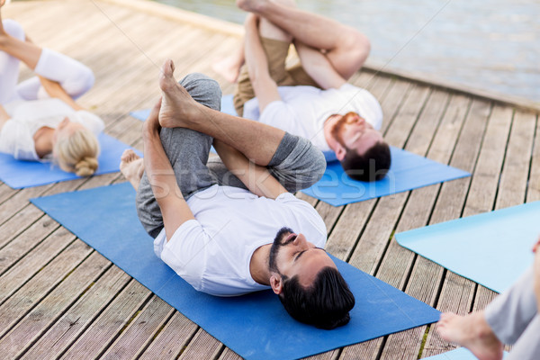 people making yoga in supine pigeon pose outdoors Stock photo © dolgachov