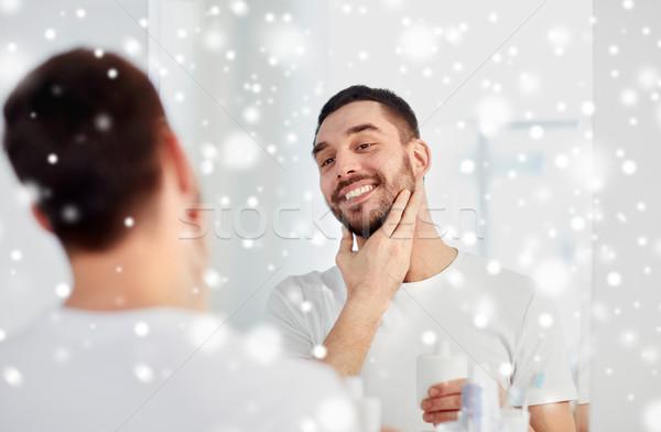 happy man applying aftershave at bathroom mirror Stock photo © dolgachov