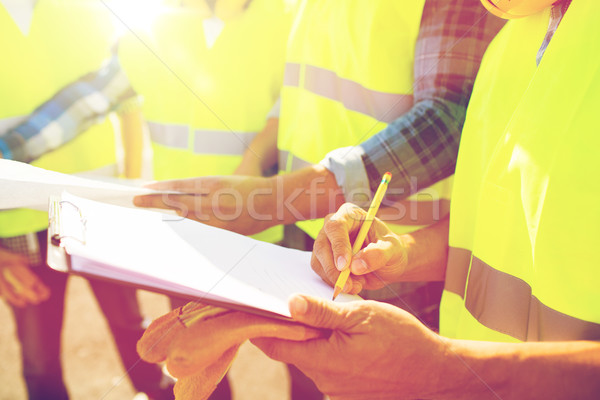 close up of builders in vests writing to clipboard Stock photo © dolgachov