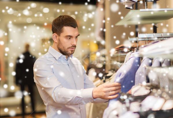 Gelukkig jonge man kiezen kleding kleding store Stockfoto © dolgachov