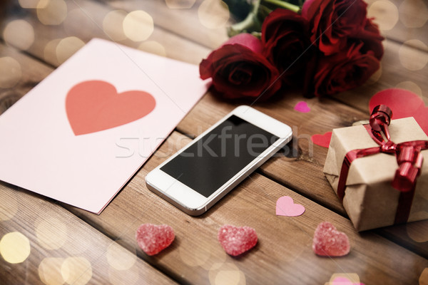 close up of smartphone, gift, red roses and hearts Stock photo © dolgachov