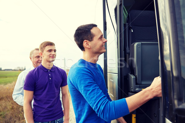 group of happy male passengers boarding travel bus Stock photo © dolgachov