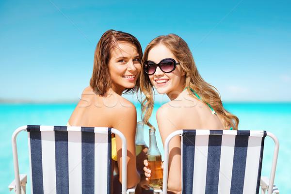Felice giovani donne bevande prendere il sole spiaggia estate Foto d'archivio © dolgachov