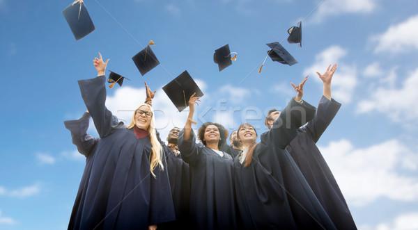 happy students throwing mortar boards up Stock photo © dolgachov