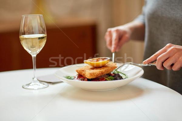 woman eating fish salad at cafe or restaurant Stock photo © dolgachov