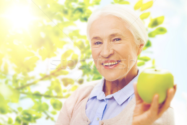 happy senior woman with green apple at home Stock photo © dolgachov