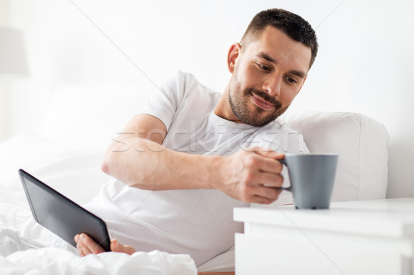man with tablet pc drinking coffee in bed at home Stock photo © dolgachov