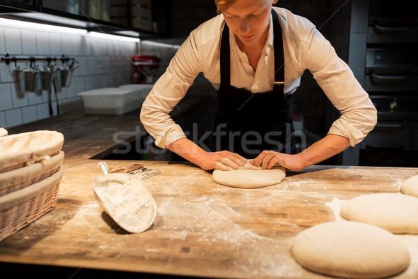 chef or baker making dough at bakery Stock photo © dolgachov