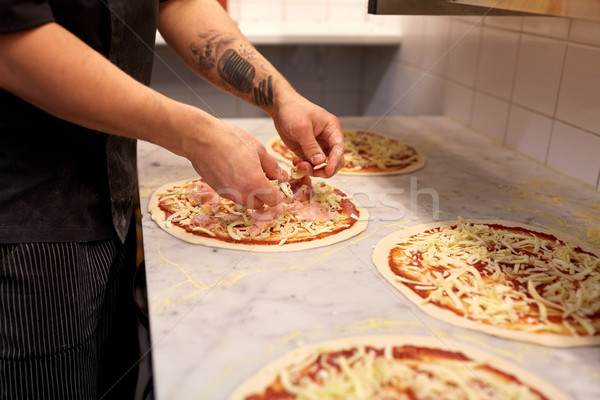 cook hands adding champignons to pizza at pizzeria Stock photo © dolgachov