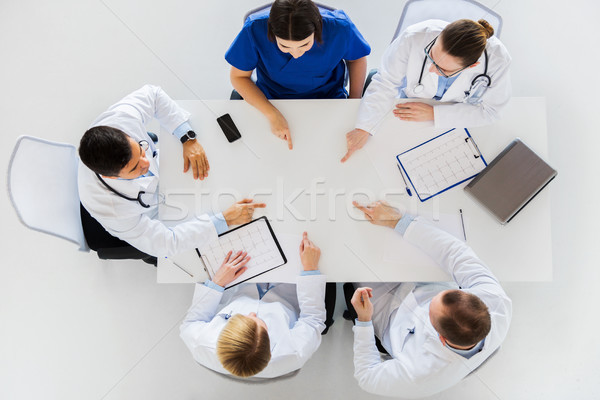 group of doctors with cardiograms working at table Stock photo © dolgachov