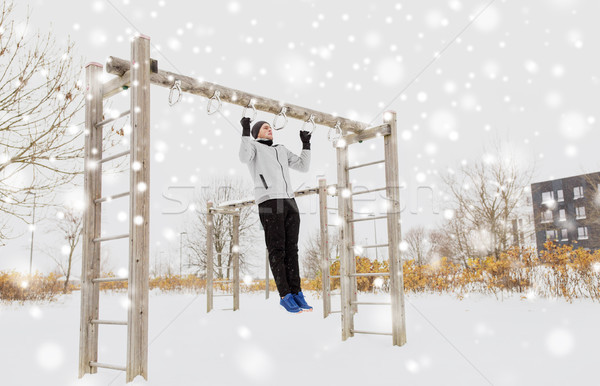 young man exercising on horizontal bar in winter Stock photo © dolgachov