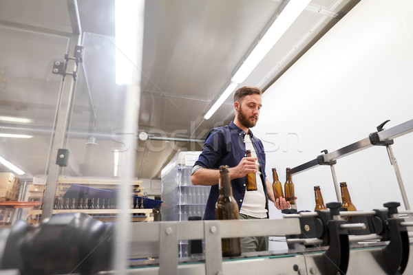 men with bottles on conveyor at craft beer brewery Stock photo © dolgachov