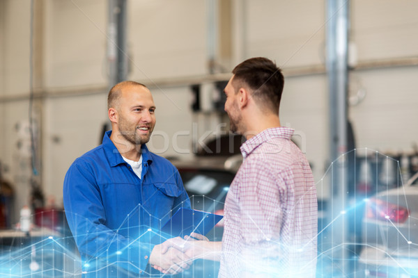 Stock photo: auto mechanic and man shaking hands at car shop