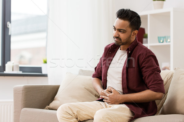 Stock photo: unhappy man suffering from stomach ache at home