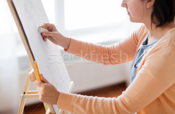 artist with eraser drawing picture at art studio Stock photo © dolgachov