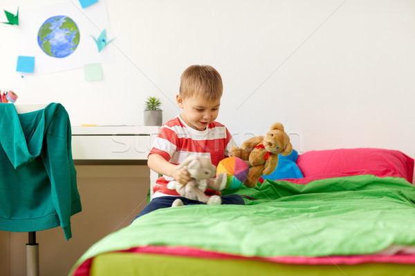 happy little boy playing with plush toys at home Stock photo © dolgachov