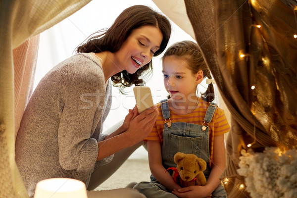 happy family with smartphone in kids tent at home Stock photo © dolgachov